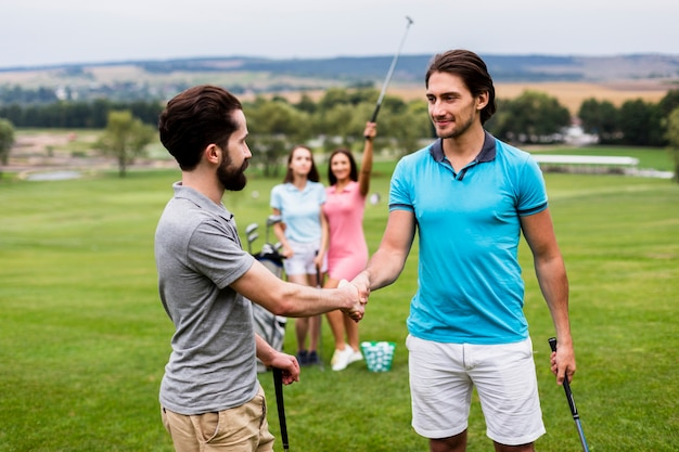 Amici di golf che stringono le mani sul campo di golf Foto Gratuite