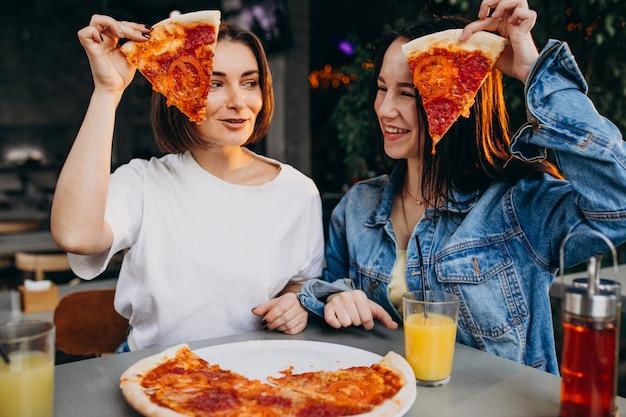 Amici di ragazza che mangiano pizza in un bar all'ora di pranzo Foto Gratuite