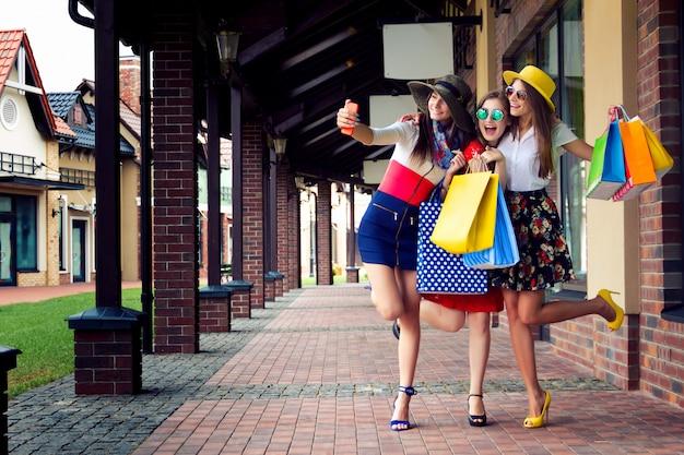 Amici di ragazze femminili abbastanza felici delle donne intelligenti in vestiti variopinti, cappelli e tacchi alti con i sacchetti della spesa che fanno selfie Foto Premium