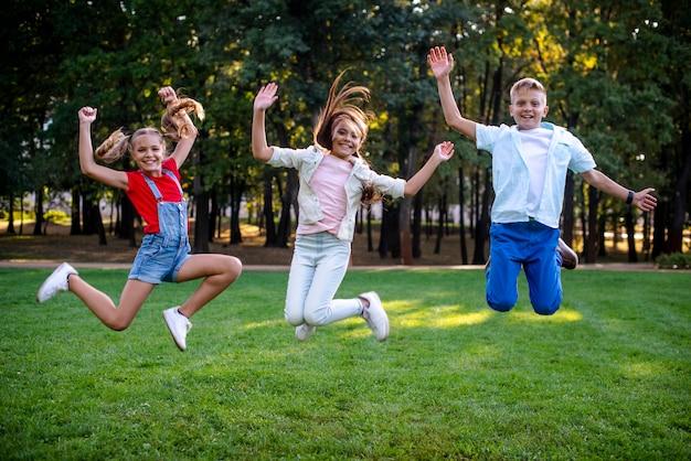 Amici di smiley che saltano guardando la fotocamera Foto Gratuite
