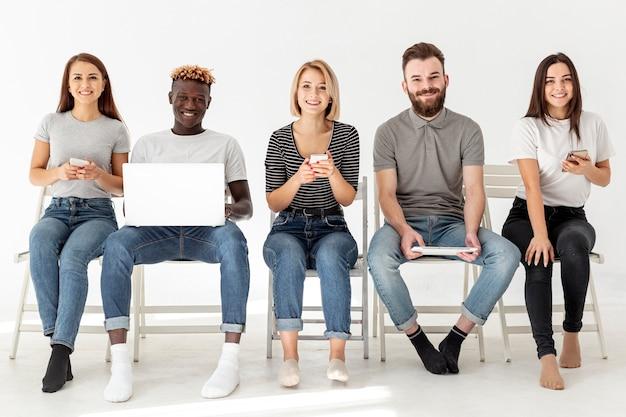 Amici di vista frontale che si siedono sulle sedie con i dispositivi moderni Foto Gratuite