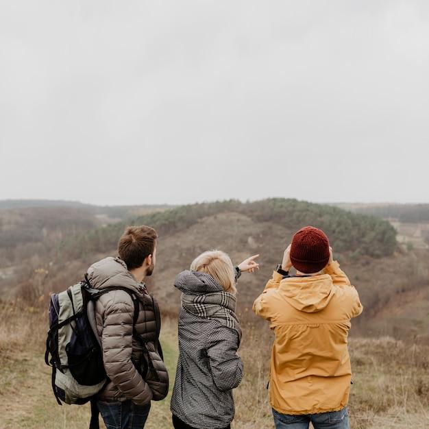 Amici di vista posteriore che godono di una vista incantevole Foto Gratuite