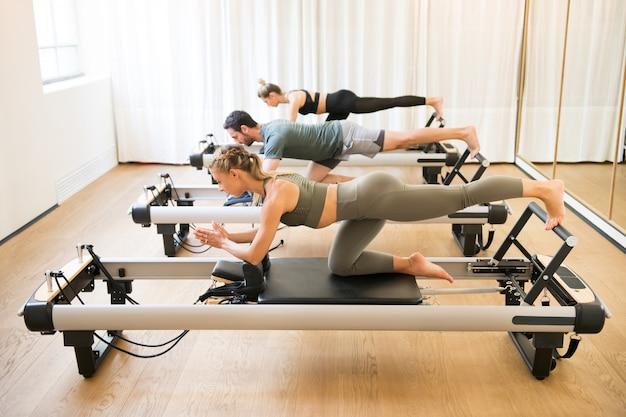Amici facendo esercizi di glutei in ginocchio pilates Foto Premium