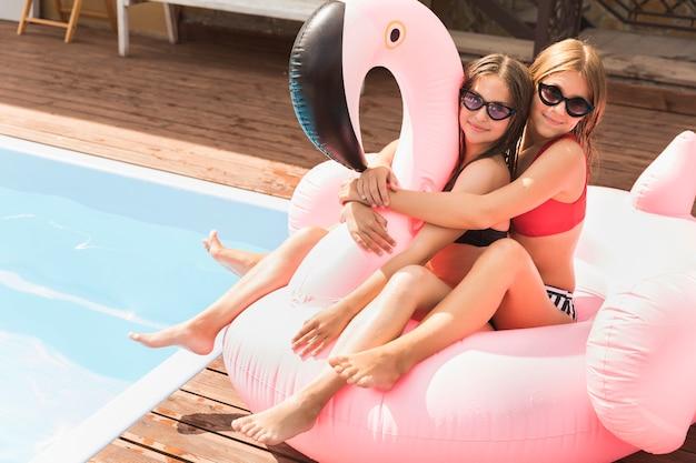 Amici felici che abbracciano la piscina vicina Foto Gratuite
