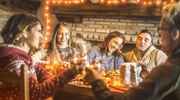 Amici felici che assaggiano la festa di divertimento dell'alimento dolce di natale a casa Foto Premium