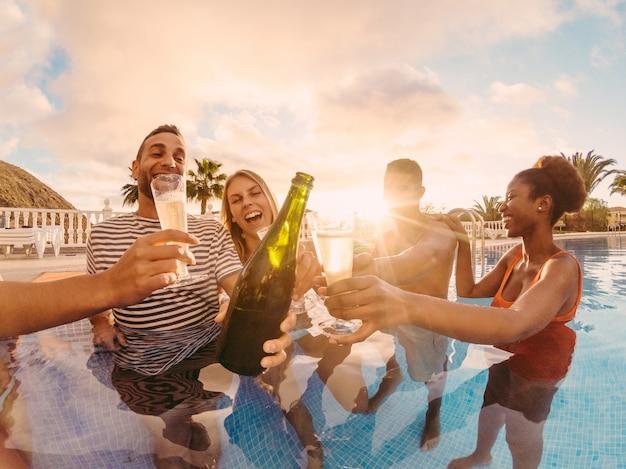 Amici felici che incoraggiano con champagne in festa in piscina al tramonto Foto Premium