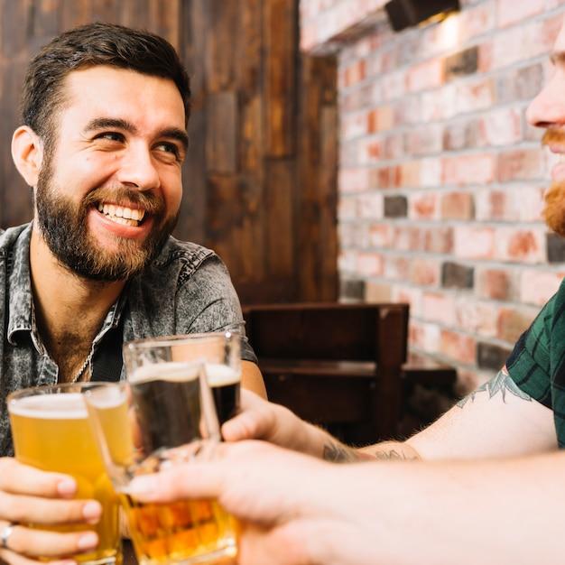 Amici felici che tostano i vetri delle bevande alcoliche nel bar Foto Gratuite