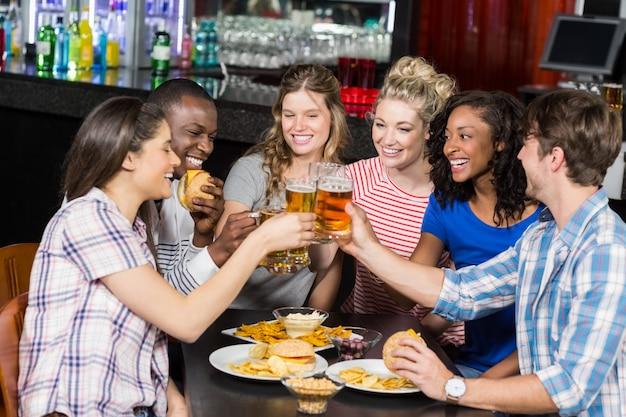 Amici felici con un drink e hamburger Foto Premium