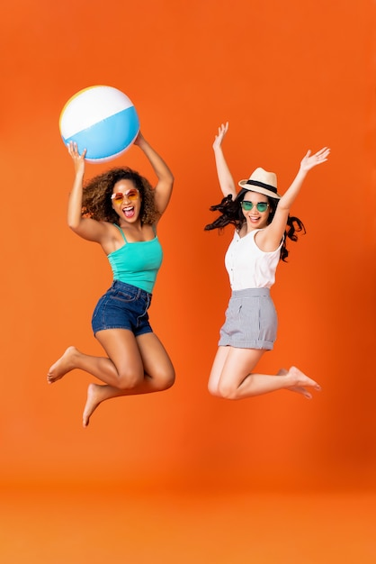 Amici felici della donna in vestiti casuali di estate che saltano Foto Premium