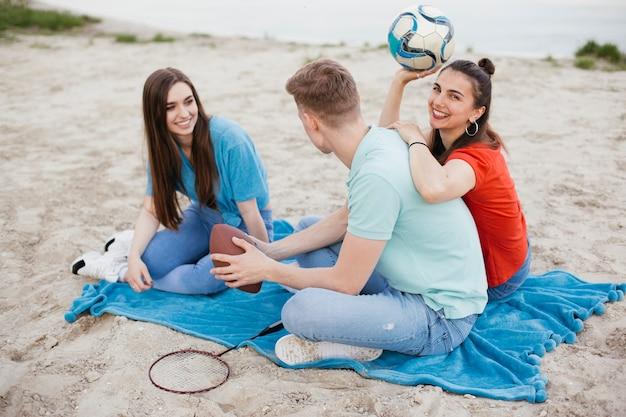 Amici felici della foto a figura intera che si siedono sulla spiaggia Foto Gratuite