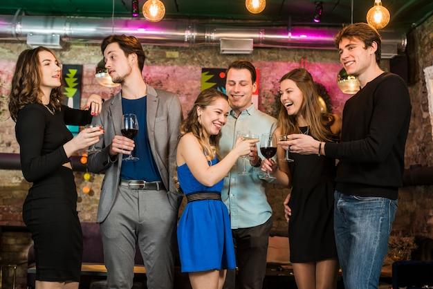 Amici felici di sesso maschile e femminile, bere e tostare cocktail in un bar Foto Gratuite