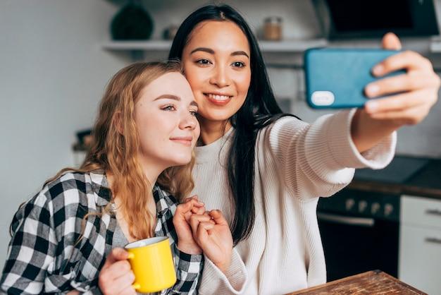 Amici femminili che prendono selfie a casa Foto Gratuite