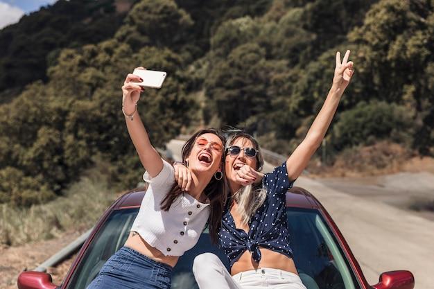 Amici femminili che si siedono sul cappuccio dell'automobile che prende autoritratto Foto Gratuite