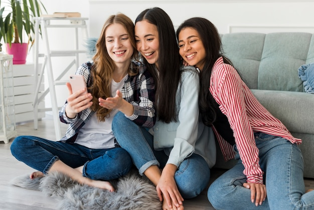 Amici gioiosi prendendo selfie su smartphone Foto Gratuite
