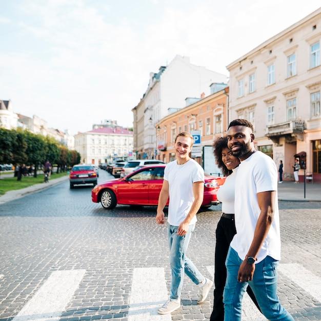 Amici interculturali che attraversano insieme la zebra Foto Gratuite