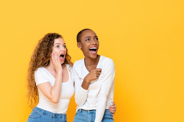 Amici interrazziali colpiti emozionanti della donna che guardano da parte isolato sulla parete gialla Foto Premium