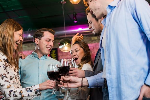 Amici maschi e femminili che ridono al bar sorseggiando un drink Foto Gratuite