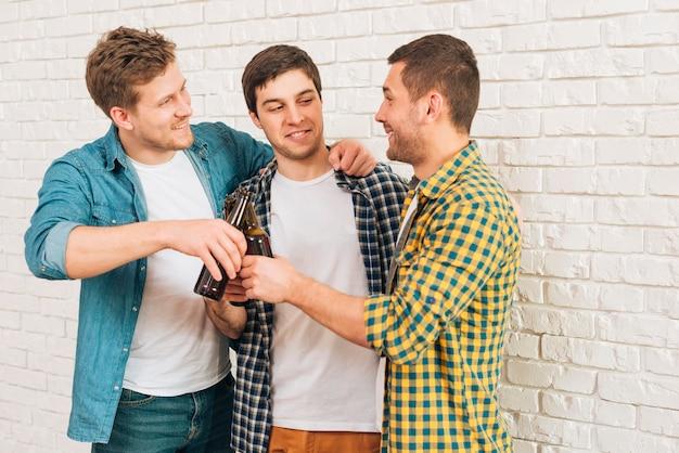Amici maschii felici che stanno contro la parete bianca che tosta le bottiglie di birra Foto Gratuite