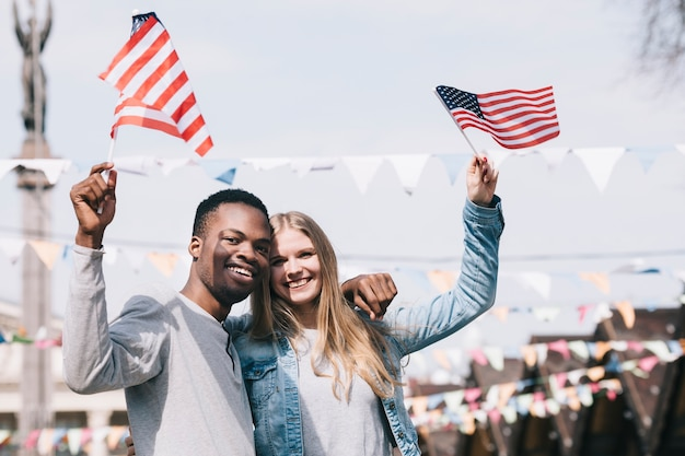 Amici multietnici che tengono le bandiere americane in mani tese Foto Gratuite