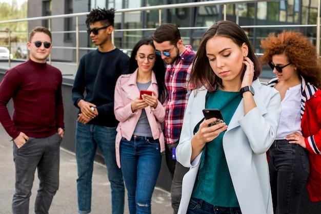 Amici multietnici che utilizzano telefono cellulare all'aperto Foto Gratuite