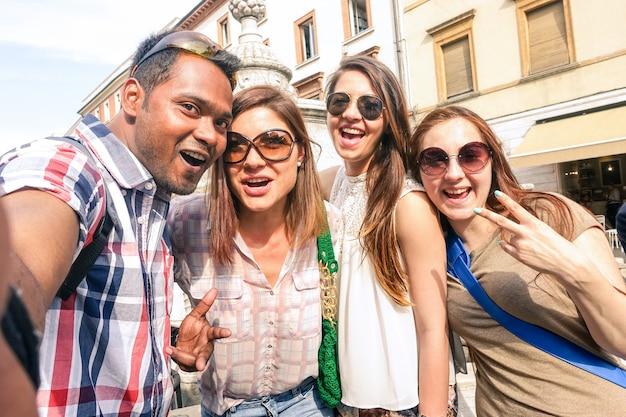 Amici multirazziali prendendo selfie al tour della città Foto Premium
