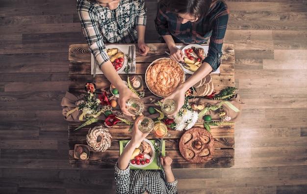 Amici o famiglia in vacanza a tavola festiva con carne di coniglio, verdure, torte, uova, vista dall'alto. Foto Premium