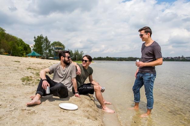 Amici rilassati con bevande sulla spiaggia Foto Gratuite