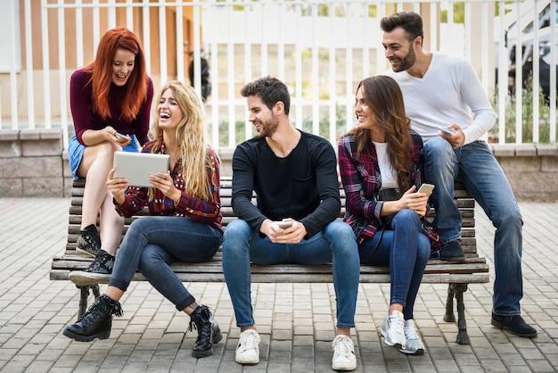 Amici seduti su una panca di legno in strada e guardando una tavoletta di una ragazza Foto Gratuite