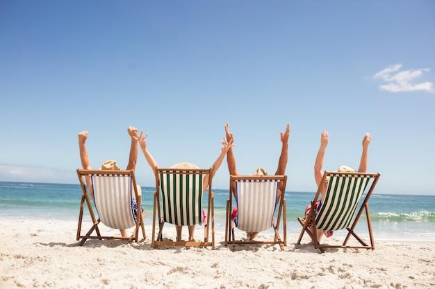 Amici senior che si siedono nella sedia di spiaggia Foto Premium