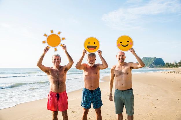 Amici senior divertendosi in spiaggia Foto Premium