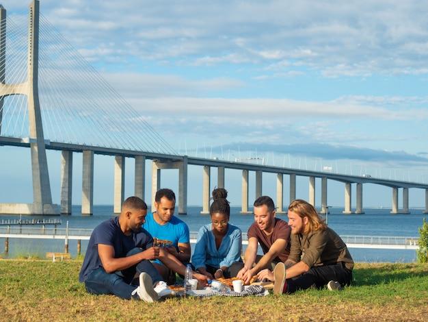 Amici sorridenti che hanno picnic in parco Foto Gratuite