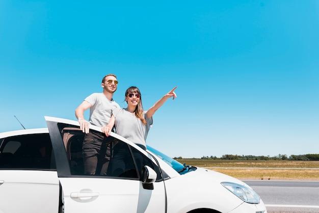 Amici sorridenti che si siedono su un'auto che indica a qualcosa Foto Gratuite