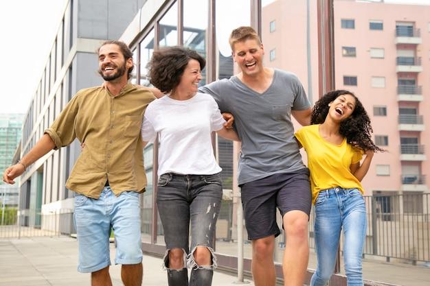 Amici spensierati felici che camminano fuori e si divertono Foto Gratuite