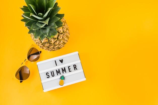 Amo la scatola luminosa estiva; occhiali da sole e ananas su sfondo giallo Foto Gratuite