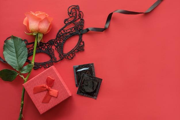 Amore, passione, sex romance piatto disteso, mock up con rosa rossa, maschera di pizzo, confezione regalo Foto Premium