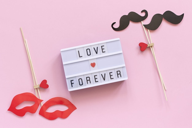 Amore per sempre testo di casella di luce, paio di baffi di carta, puntelli di labbra sul rosa Foto Premium