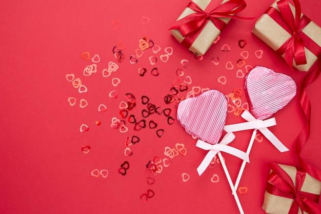 Amore, san valentino mock up, con lecca-lecca a forma di cuore, confezione regalo e glitter isolato su sfondo rosso, copia spazio. Foto Premium