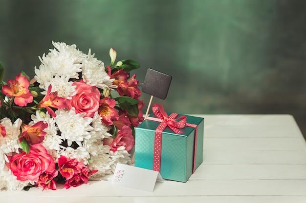Amore sfondo con rose rosa, fiori, regalo sul tavolo Foto Gratuite