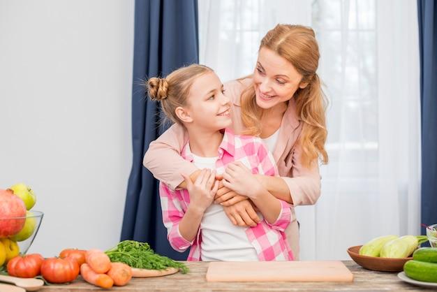 Amorevole madre e sua figlia in piedi dietro il tavolo con verdure Foto Gratuite