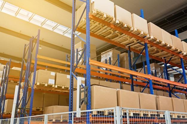 Ampio magazzino di hangar di aziende industriali e logistiche. scaffali lunghi con una varietà di scatole. spazio di industria e scatola dell'hardware per la consegna, concetto del carico di stoccaggio di distribuzione di logistica di affari. Foto Premium