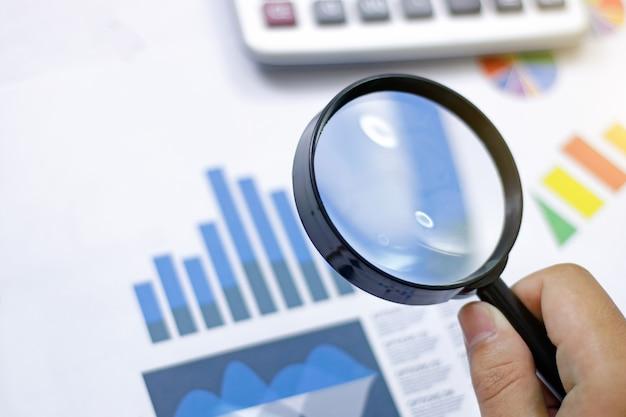 Analisi e statistiche aziendali. uomo d'affari facendo uso di una lente d'ingrandimento su un grafico del mercato azionario Foto Premium