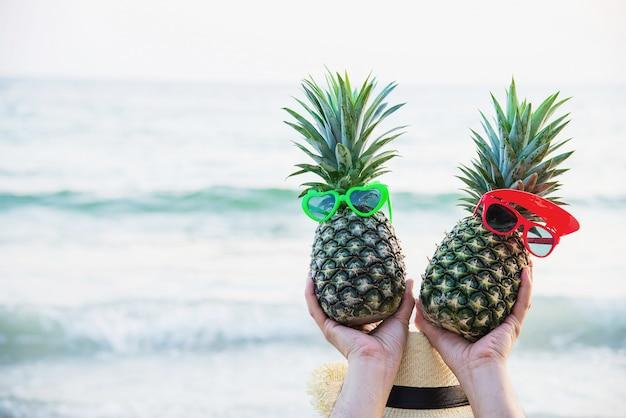 Ananas fresco delle coppie adorabili che mettono i vetri della ragazza e del ragazzo in mani turistiche con l'onda del mare - divertimento felice con il concetto sano di vacanza Foto Gratuite