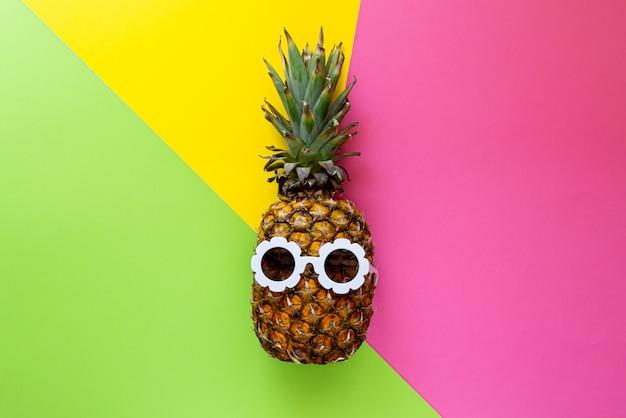 Ananas in occhiali da sole bianchi sui precedenti variopinti, concetto creativo di estate Foto Premium