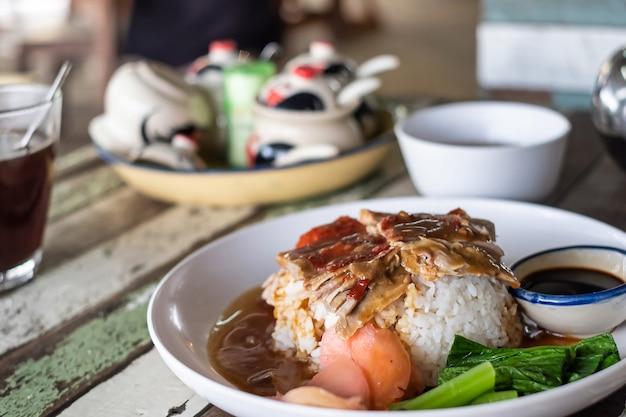 Anatra arrosto barbecue su riso nella ricetta del menu tailandese Foto Premium