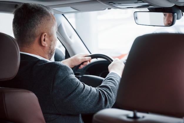 Andare alla riunione. vista da dietro dell'uomo d'affari maggiore in abiti ufficiali alla guida di una nuova auto moderna Foto Gratuite