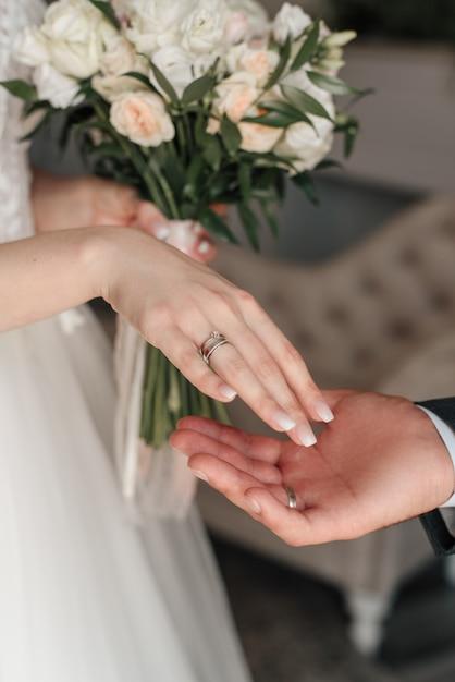 Anelli della sposa e dello sposo sullo sfondo del bouquet Foto Premium