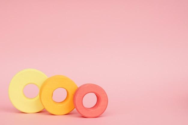 Anelli di legno per bambini di arancio e giallo su sfondo rosa Foto Premium