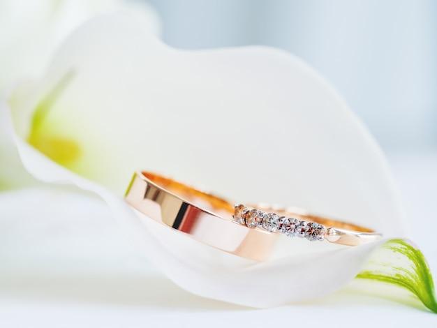 Anelli di nozze d'oro con diamanti si trovano all'interno del fiore di giglio di calla. simbolo di amore e matrimonio, accessori tradizionali costosi per la sposa e lo sposo. Foto Premium