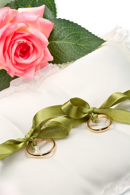 Anelli di nozze d'oro sul cuscino bianco con rosa Foto Premium