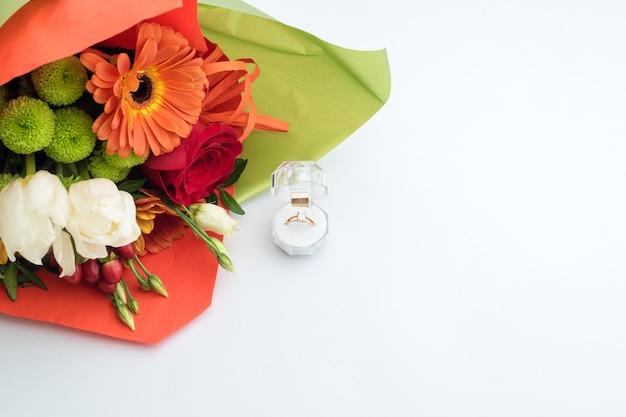 Anello di fidanzamento in confezione regalo con brillante mazzo di fiori. l'offerta di sposarsi. regalo per san valentino. proposta di matrimonio per la donna amata. simbolo di amore e matrimonio. Foto Premium